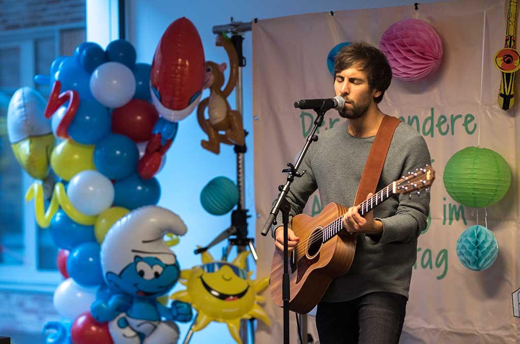 """2017 spielt Max Giesinger ein Kinderklinikkonzert unplugged. Viele Luftballons schmücken seine kleine Bühne, während er Hits wie """"Wenn Sie Tanzt"""" und """"80 Millionen"""" performt."""
