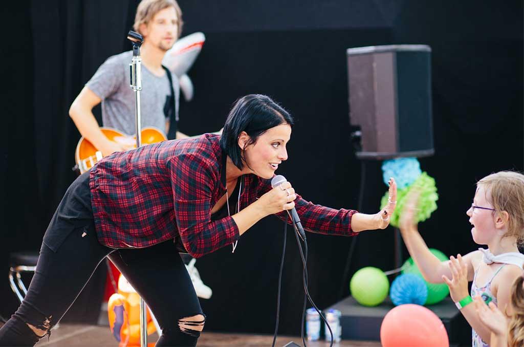 Die Frontfrau von Silbermond, Stefanie Kloß, schlägt in die Hand eines Kindes ein, während sie und ihre Band ihr Kinderklinikkonzert 2016 spielen.
