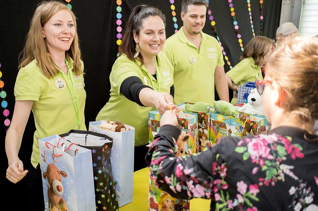 Junge Menschen geben Geschenktüten an die Kinder des Kinderklinikkonzertes aus