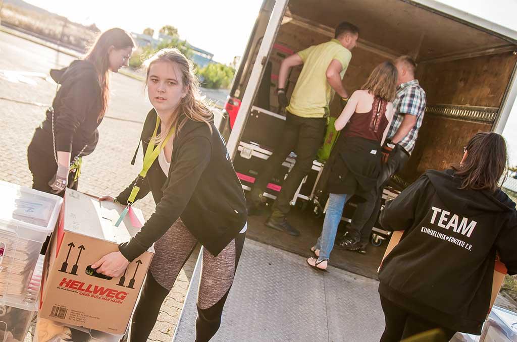 Studierende packen LKW aus, um das Kinderklinikkonzert aufzubauen