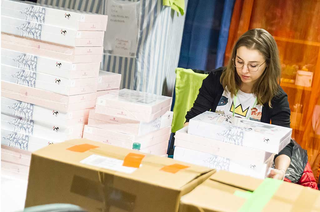 Eine junge, blonde Dame mit Brille sitzt zwischen unzähligen Paket-Stapeln.